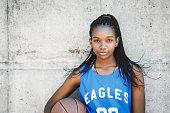 Confident female basketball player holding ball