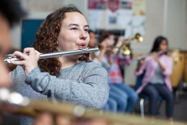 Confident female brunette student practicing flute in band orchestra class stock photo