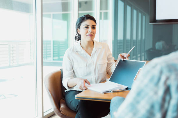 Confident female business owner listens to man stock photo