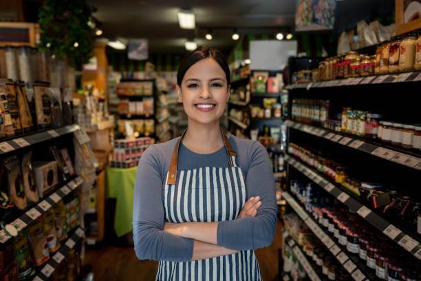 카메라 웃 고 직면 하는 동안 선반 사이 슈퍼마켓 서의 자신감 여성 비즈니스 소유자 - 시장 소매점 뉴스 사진 이미지