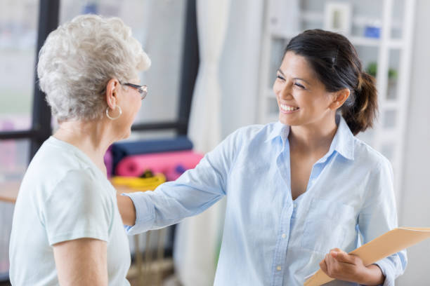 confident female chiropractor talks with new patient - alternative medicine stock pictures, royalty-free photos & images