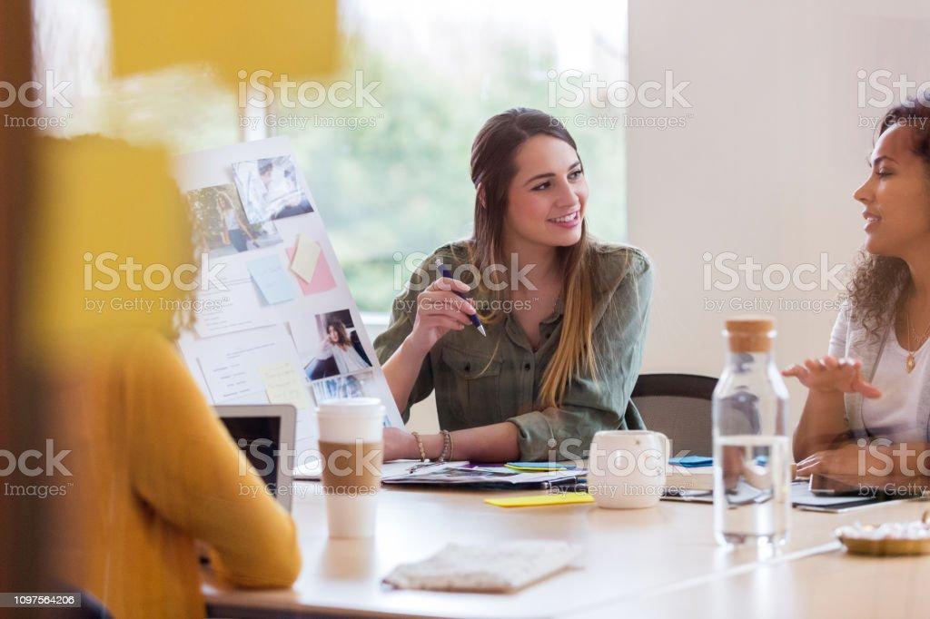 Beautiful female creative professional shows an idea board to her...