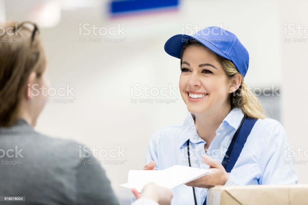 Confident female delivery person talks with customer stock photo