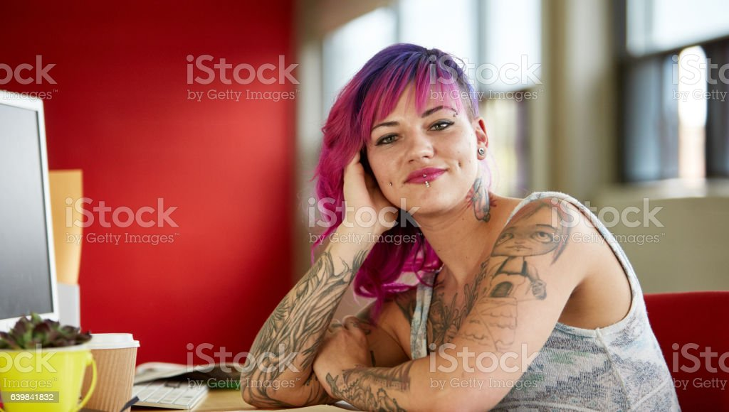 Confident female designer working in red creative office space stock photo