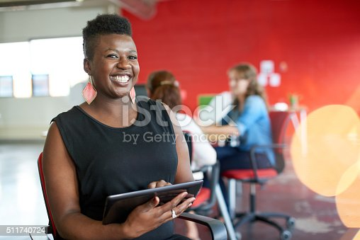 istock Confident female designer working on a digital tablet in red 511740724
