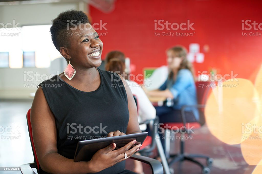 Confident female designer working on a digital tablet in red royalty-free stock photo