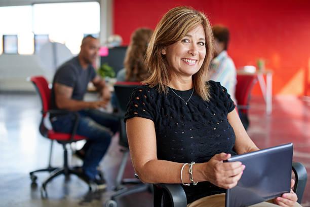 confiant femme styliste travaillant sur une tablette numérique en rouge - directrice photos et images de collection