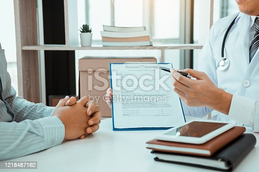 1026367516 istock photo Confident female doctor reviews patient medical information and pointing to medical forms. 1218487162