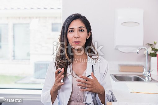 Personal perspective view of a female doctor talking with a patient during a telemedicine appointment.