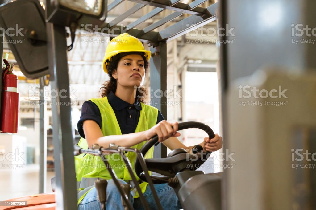 Confident female driving forklift in factory Confident female driver driving forklift. Mid adult woman is working in distribution warehouse. She is wearing hardhat and reflective clothing in factory. 30-34 Years Stock Photo