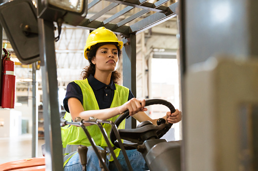 Confident Female Driving Forklift In Factory Stock Photo - Download Image Now
