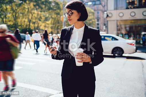 istock Confident female entrepreneur using mobile phone for sending message standing on crowded road in new york, serious businesswoman reading information from web page on mobile holding mock up coffee cup 897391466