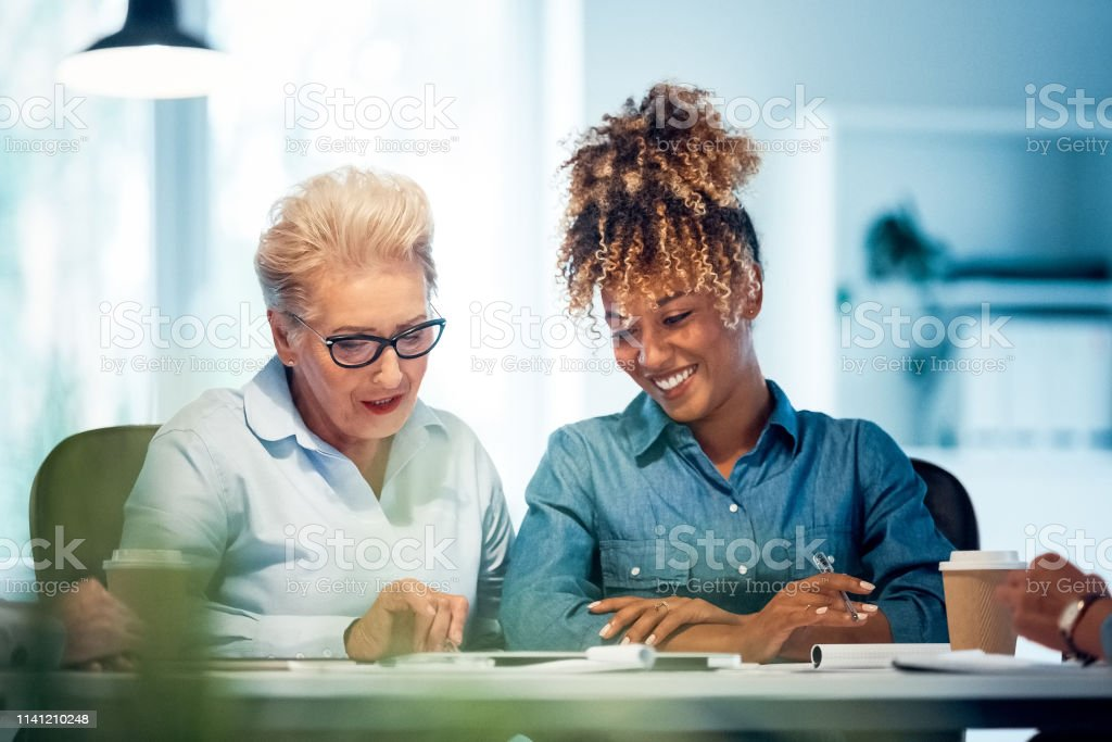 Confident female expertise planning new project Confident female expertise planning new project for business. Businesswomen are discussing over document. They are working together in office. 35-39 Years Stock Photo