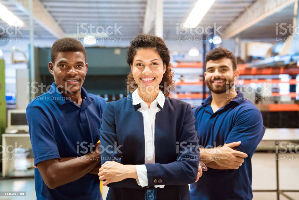 Confident female inspector standing ahead of team Confident female inspector standing ahead of team. Portrait of engineers are in manufacturing industry. They are smiling. 20-24 Years Stock Photo