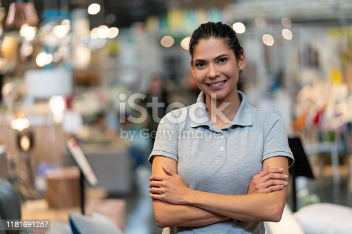 Confident female manager of a furniture store looking at camera smiling with arms crossed - Focus on foreground