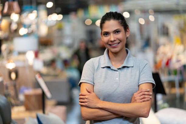 zelfverzekerde vrouwelijke manager van een meubelwinkel kijken naar camera glimlachend met armen gekruist - verkoopster stockfoto's en -beelden