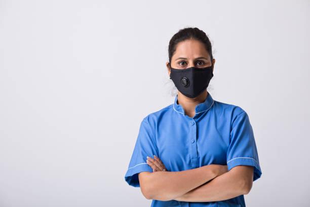 Zuversichtliche Krankenschwester trägt schützende Gesichtsmaske, um eine Viruserkrankung zu verhindern – Foto