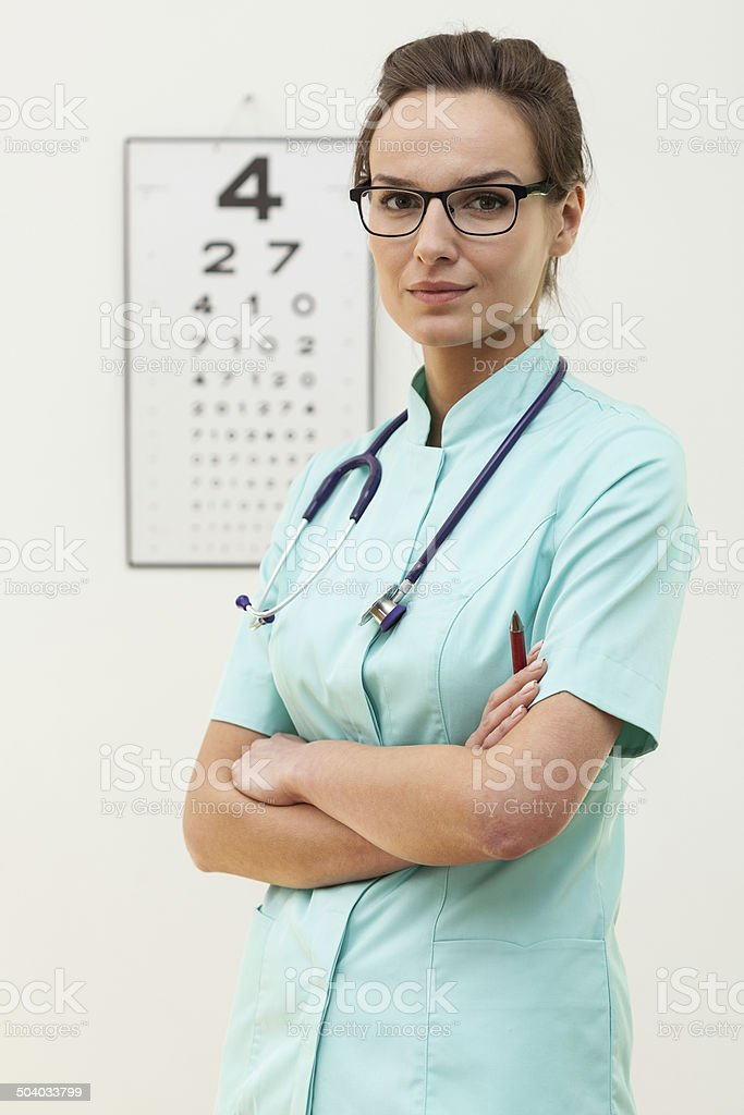 Confident female optometrist standing with arms crossed stock photo