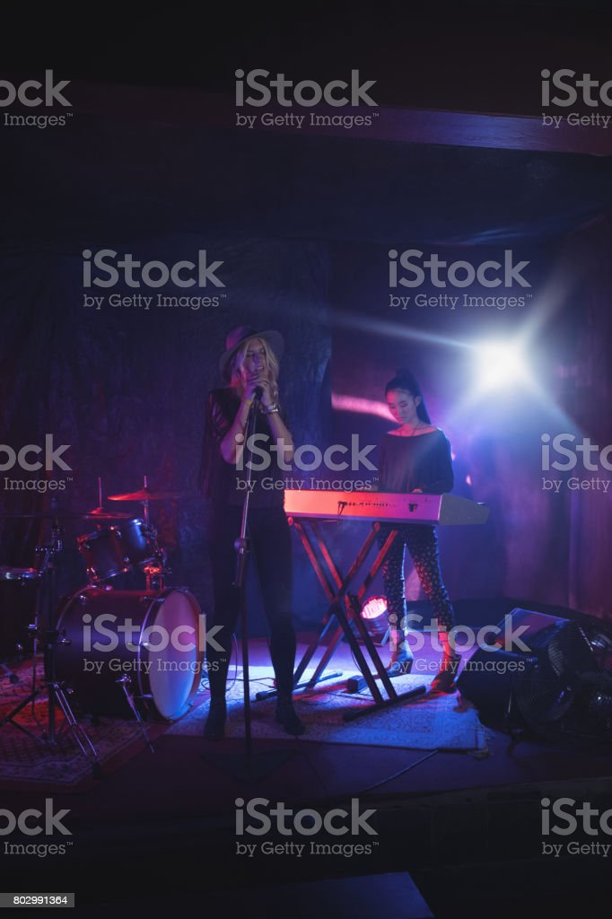 Confident female performers performing on stage in nightclub stock photo