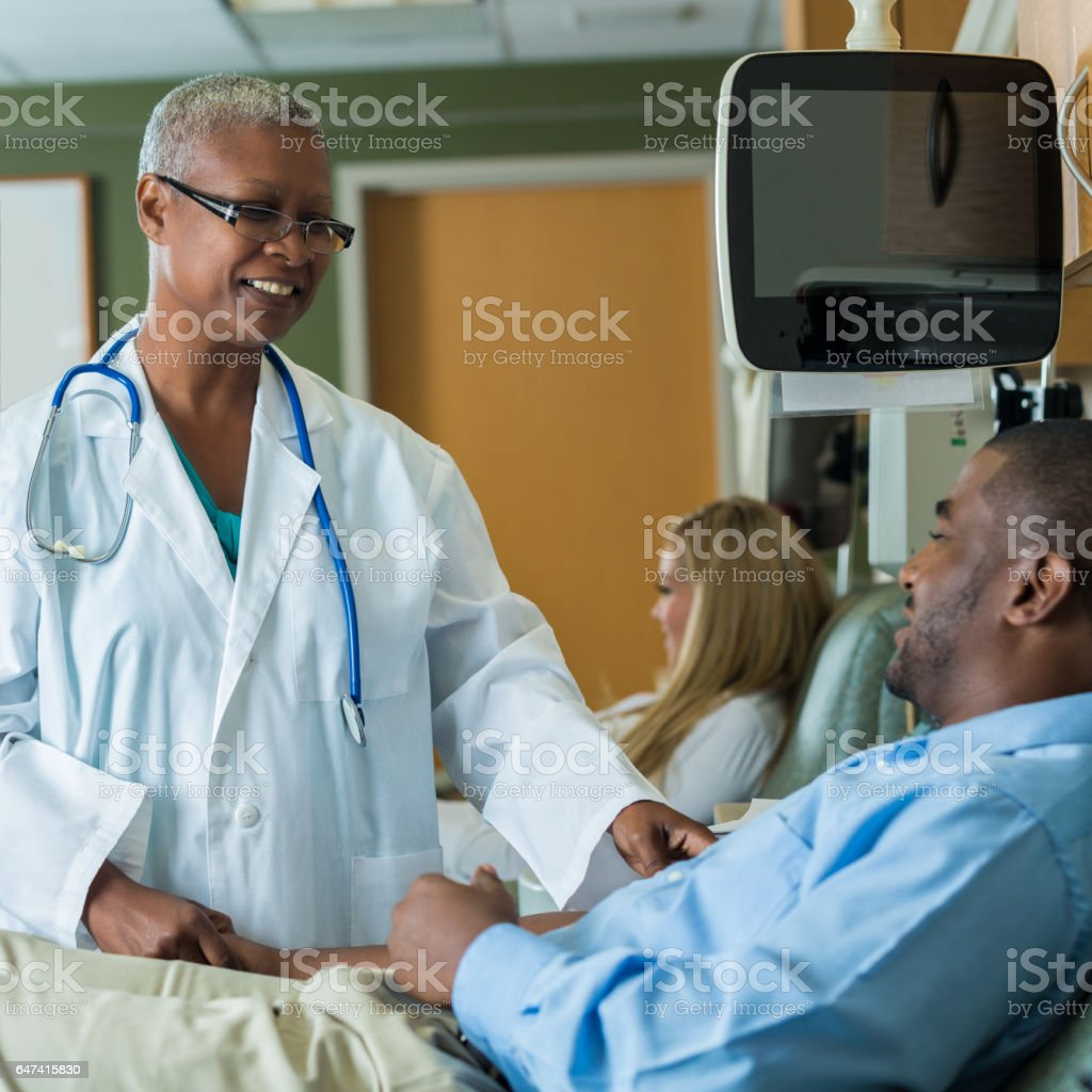 Confident female phlebotomist talks with male blood donor stock photo