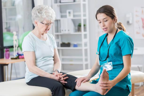 自信を持って女性理学療法士女性彼女の足を伸ばすことができます。 ストックフォト