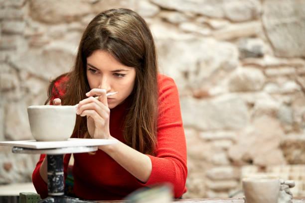 confiante potter feminino moldar argila em classe - cerâmica artesanato - fotografias e filmes do acervo