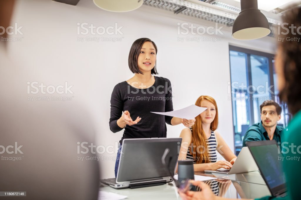 Confident female professional discussing with colleagues - Royalty-free Adult Stock Photo