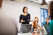 istock Confident female professional discussing with colleagues 1150572145
