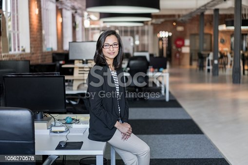 Portrait of confident female professional sitting on desk. Beautiful young businesswoman is at creative workplace. She is wearing blazer.