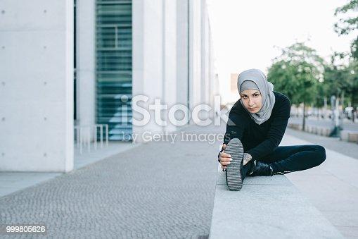 istock Confident female runner stretching her legs. 999805626