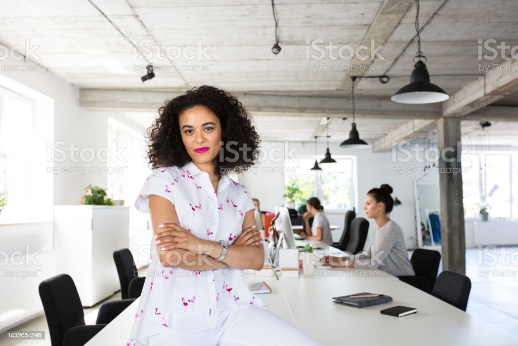 Confident female software engineer in modern office Portrait of confident young woman sitting at the table with colleagues working on computer in background. 20-24 Years Stock Photo
