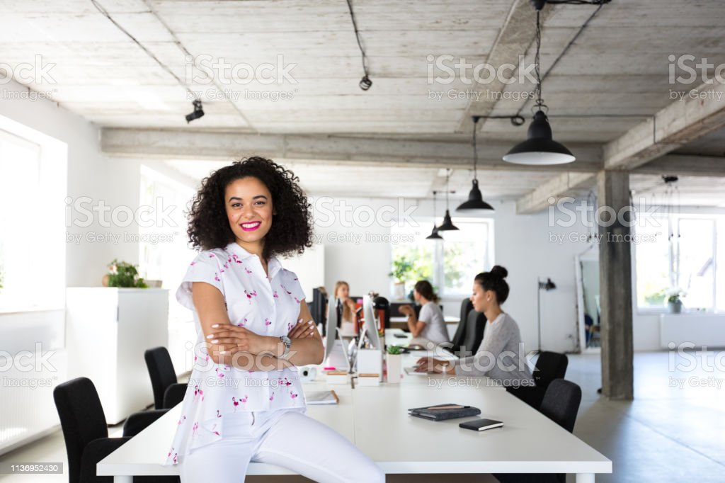 Confident female software engineer in modern office Portrait of young woman sitting at the table with colleagues working on computer in background. 20-24 Years Stock Photo