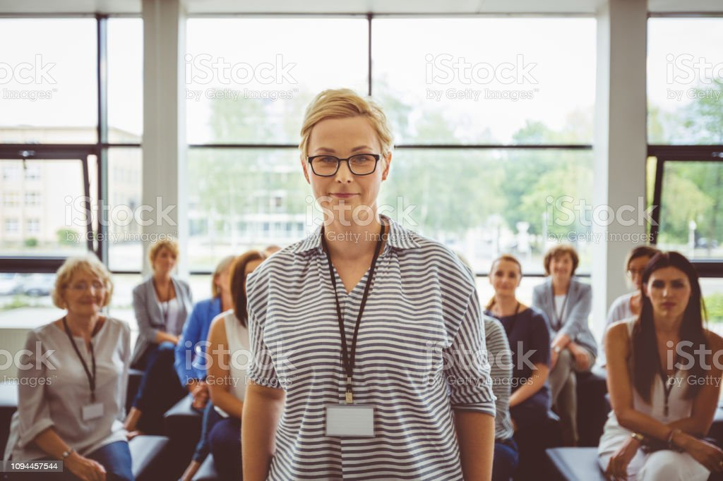 Confident female speaker with audience in background Portrait of young female speaker with group of women sitting in background Adult Stock Photo
