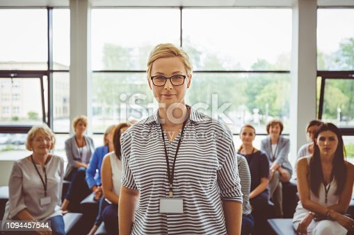 854811490istockphoto Confident female speaker with audience in background 1094457544