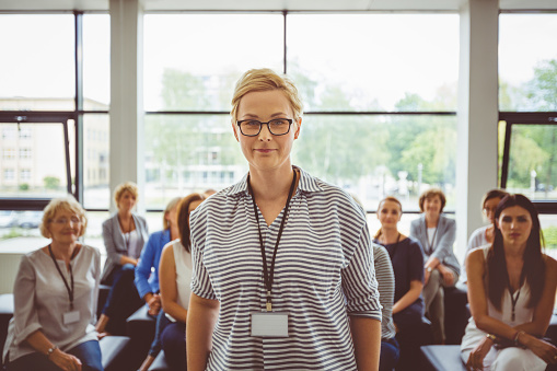 Confident Female Speaker With Audience In Background Stock Photo - Download Image Now