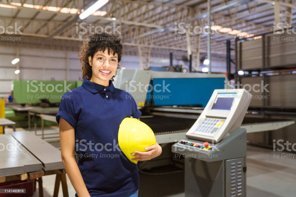 Confident female trainee standing in industry Portrait of smiling female trainee holding yellow hardhat. Confident engineer standing in industry. She is wearing uniform. 30-34 Years Stock Photo
