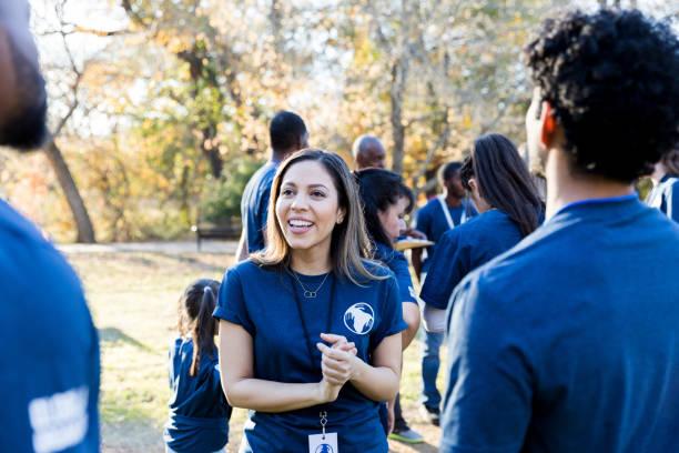 confident female volunteer talks with friends - organizzazione no profit foto e immagini stock