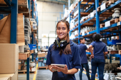 Portrait of a female factory employee with a digital tablet looking at camera and smiling. Woman warehouse worker with people in background.