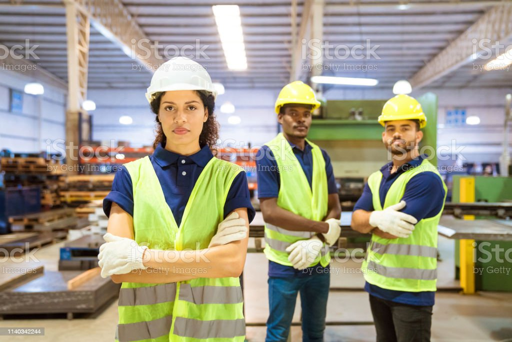 Confident female worker standing ahead of team Confident female worker standing ahead of team. Portrait of engineers are wearing reflective clothing and hardhats. Expertise are in manufacturing industry. 20-24 Years Stock Photo