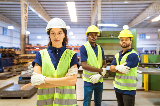 Confident Female Worker Standing Ahead Of Team Stock Photo - Download Image Now