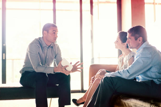 Confident financial planner talking to couple stock photo