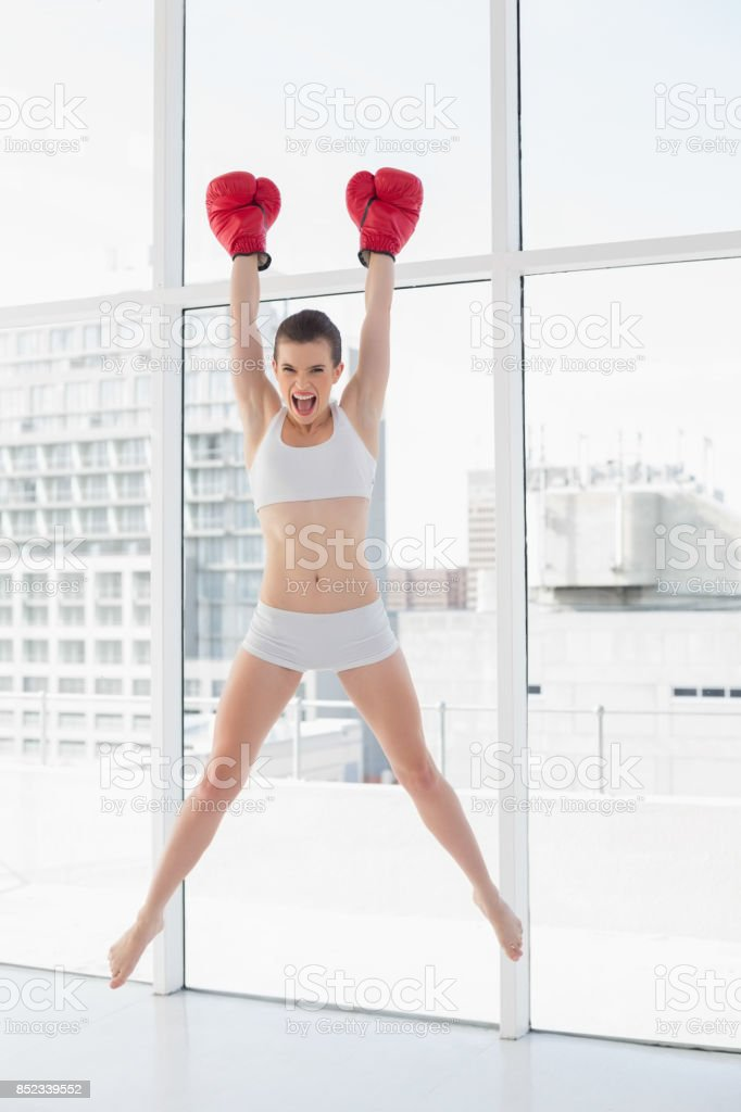 Confident fit brown haired model in sportswear jumping and wearing boxing gloves stock photo