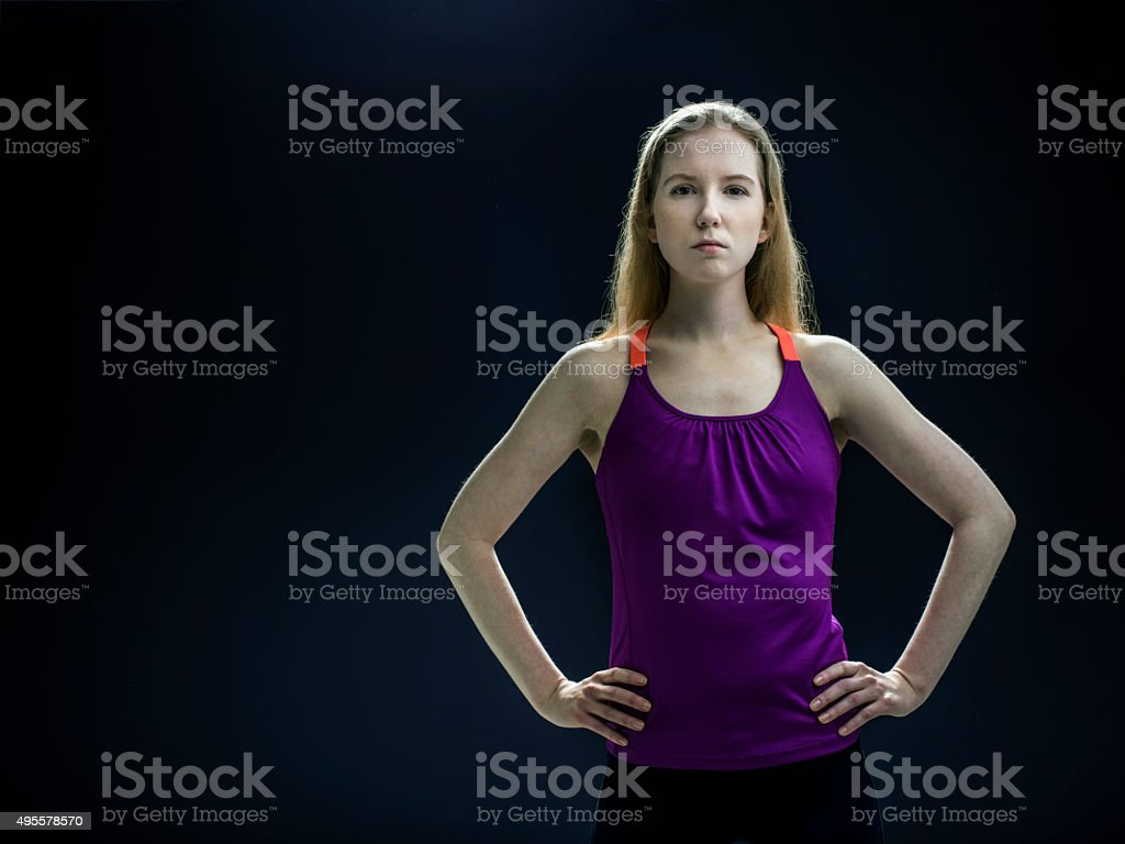 Confident fit woman standing with hands on hip stock photo