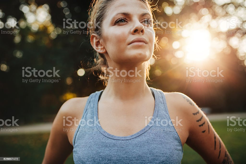 Confident fitness model in park stock photo