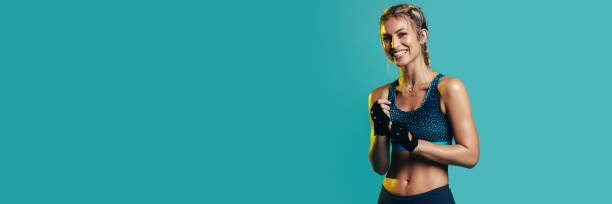 Confident fitness woman on blue background stock photo
