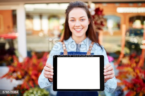 863476166istockphoto Confident florist showing digital tablet 576575064