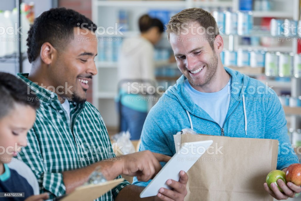 Confident food bank manager checks inventory stock photo