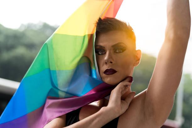 vertrouwen gay boy holding regenboogvlag - drag queen stockfoto's en -beelden