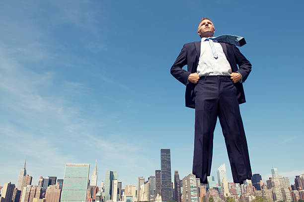 Confident Giant Businessman Standing Tall Over City Skyline stock photo
