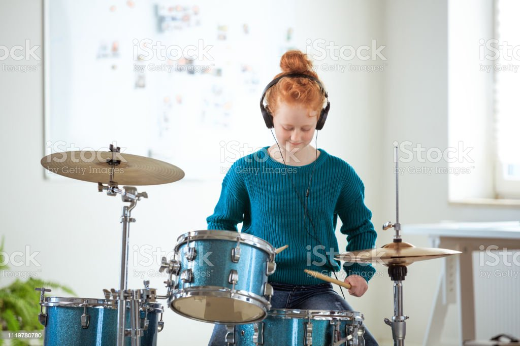 Confident girl listening music while playing drums Confident female drummer practicing in training class. Student is listening music through headphones. She is playing drums. 12-13 Years Stock Photo